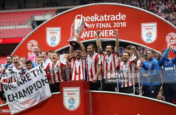 Luke Waterfall of Lincoln City lifts the trophy after the Checkatrade Trophy Final match between Shrewsbury Town and Lincoln City at Wembley Stadium...