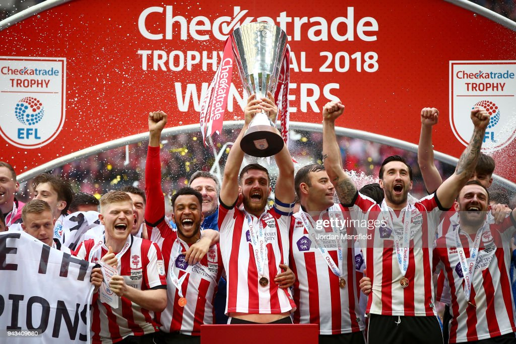 Luke Waterfall of Lincoln lifts the trophy with his teammates after victory during the Checkatrade Trophy Final between Shrewsbury Town and Lincoln City at Wembley Stadium on April 8, 2018 in London, England.