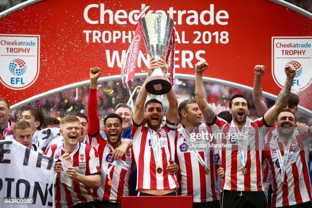 Luke Waterfall of Lincoln lifts the trophy with his teammates after victory during the Checkatrade Trophy Final between Shrewsbury Town and Lincoln...