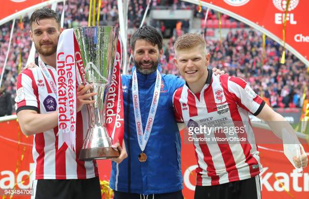 Luke Waterfall of Lincoln manager Danny Cowley and goalscorer Elliot Whitehouse pose with the trophy during the Checkatrade Trophy Final between...