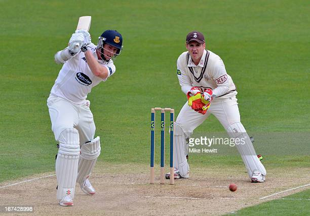 Luke Wells of Sussex hits out as wicketkeeper Steve Davies of Surrey looks on during day two of the LV County Championship Division One match between...