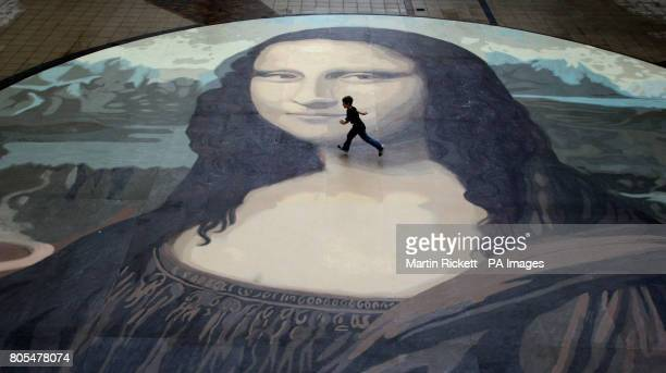 Luke WhartonJones runs across an attempt at the worlds biggest copy of the Mona Lisa during a photocall for it's unveiling at the Eagles Meadow...