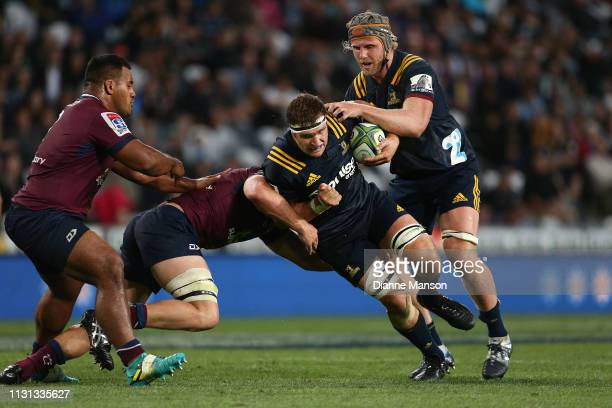 Luke Whitelock of the Highlanders is tackled by Angus ScottYoung of the Queensland Reds during the Round 2 Super Rugby match between the Otago...