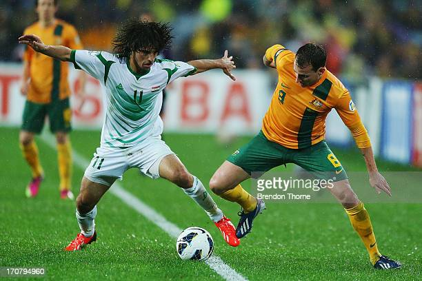Luke Wilkshere of Australia competes with Humam Tareq Faraj of Iraq during the FIFA 2014 World Cup Asian Qualifier match between the Australian...