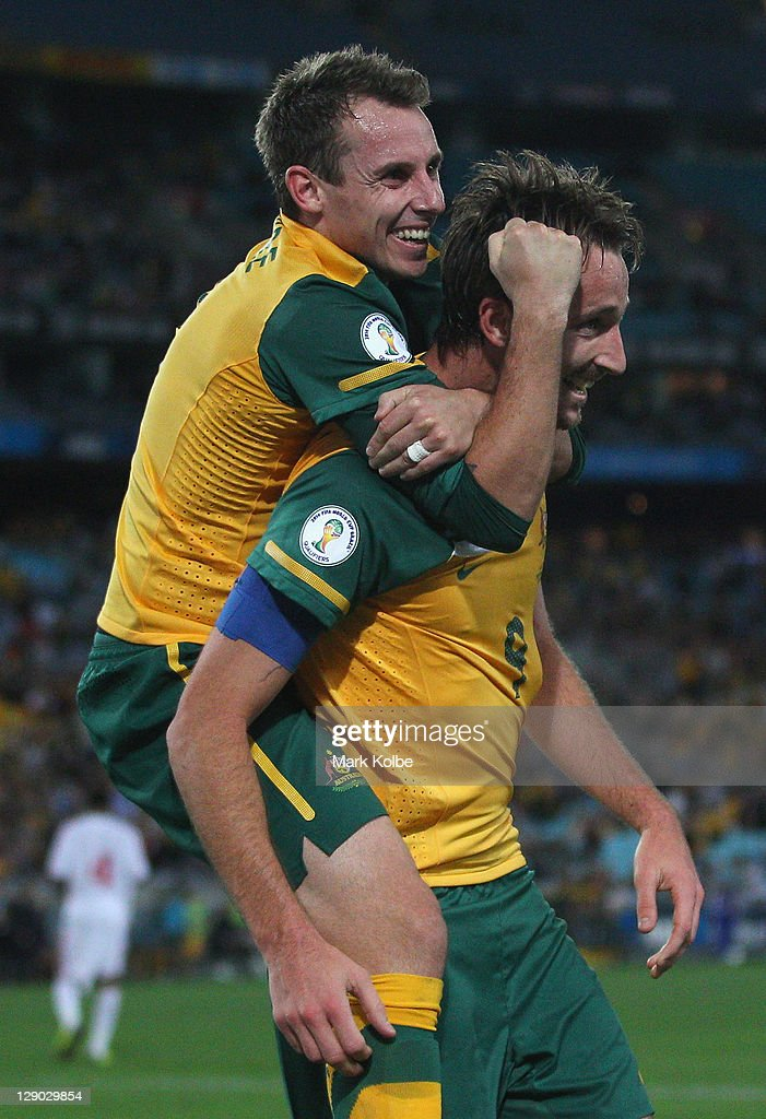 Luke Wilkshire and Josh Kennedy of the Socceroos celebrate after Kennedy scored Australia's second goal during the FIFA World Cup Asian Qualifier match between the Australian Socceroos and Oman at ANZ Stadium on October 11, 2011 in Sydney, Australia.