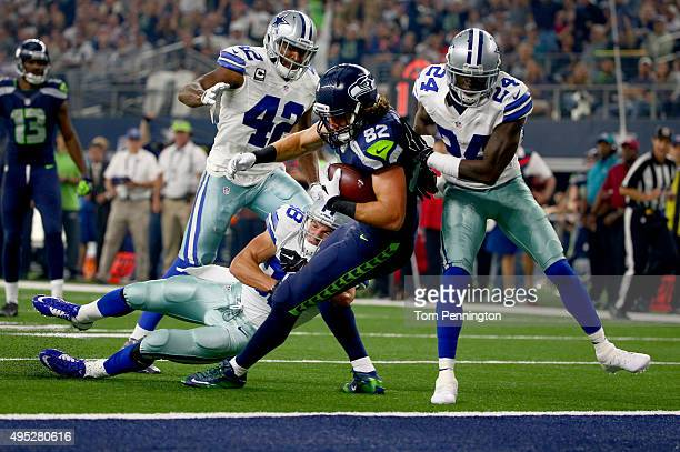 Luke Willson of the Seattle Seahawks takes the ball across the goal line to score a touchdown against Barry Church, Jeff Heath and Morris Claiborne...