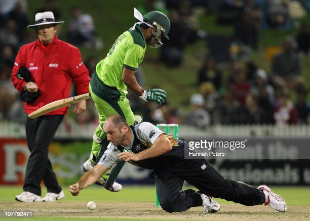 Luke Woodcock of New Zealand fields off his own bowling as he clashes with Umar Akmal of Pakistan during game two of the Twenty20 series between New...