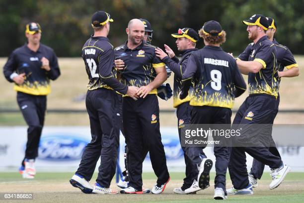 Luke Woodcock of Wellington is congratulated by team mates after dismissing Tom Latham of Canterbury during the Ford Trophy match between Canterbury...