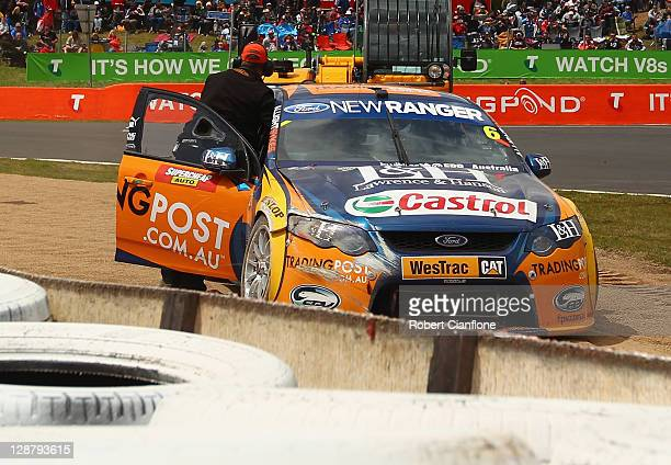 Luke Youlden driver of the Ford Performance Racing Ford has his car removed from a sandtrap after hitting the wall during the Bathurst 1000 which is...
