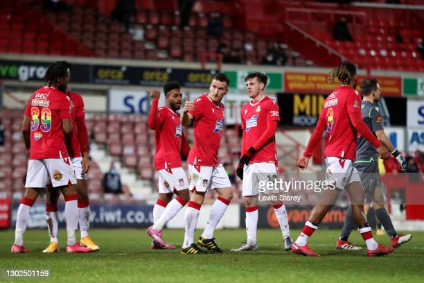 Luke Young of Wrexham celebrates with Reece Hall-Johnson and Dan Jarvis after scoring his team's second goal from the penalty spot during the...