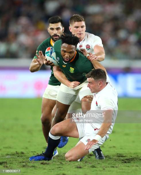 Lukhanyo Am of South Africa escapes the tackle of Owen Farrell and George Ford of England during the Rugby World Cup 2019 Final between England and...