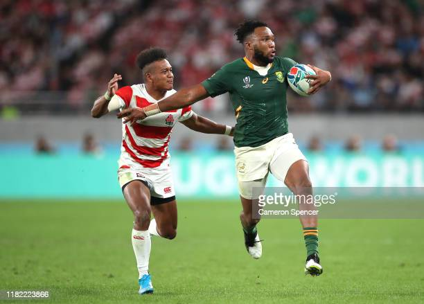 Lukhanyo Am of South Africa passes under pressure from Kotaro Matsushima of Japan during the Rugby World Cup 2019 Quarter Final match between Japan...
