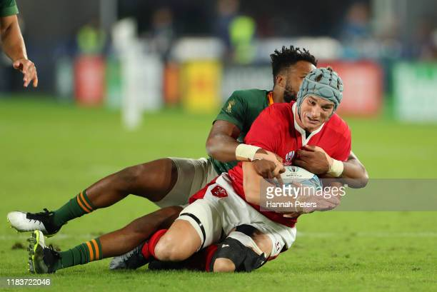 Lukhanyo Am of South Africa tackles Jonathan Davies of Wales during the Rugby World Cup 2019 SemiFinal match between Wales and South Africa at...