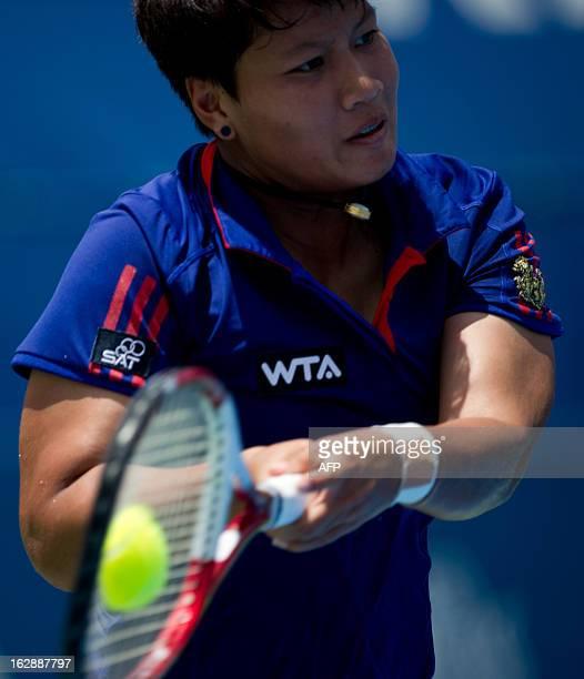 Luksika Kumkhum of Thailand hits a return against Ayumi Morita of Japan during their women's quarter-final singles match at the BMW Malaysian Open...