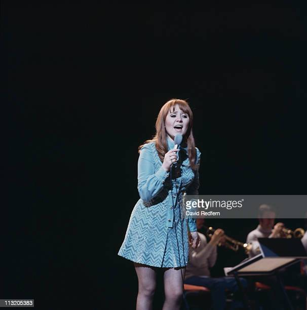 Lulu British singer singing into a microphone during a live concert performance circa 1970