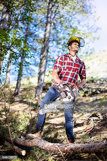 Lumberjack cutting the branch with chainsaw
