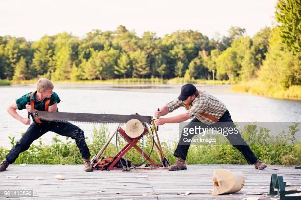 Lumberjacks sawing log at riverbank