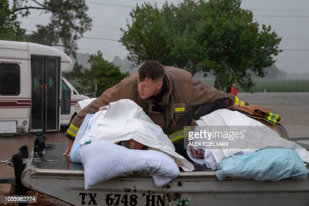 A Lumberton firefighter holds on to two nursing home patients as a member of the Cajun Navy drives his truck during the evacuation of a nursing home...