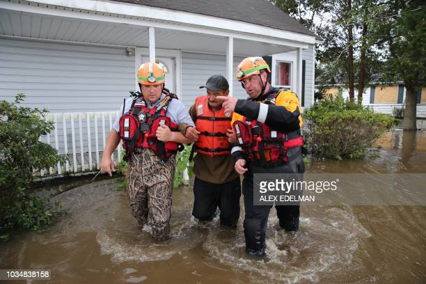 TOPSHOT Lumberton North Carolina Fire and Rescue members help a resident walk through flooded waters in Lumberton North Carolina on September 17 2018...