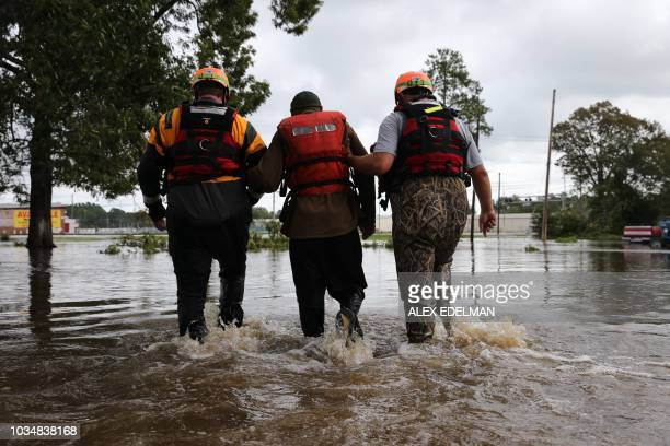 Lumberton North Carolina Fire and Rescue members help a resident walk through flooded waters in Lumberton North Carolina on September 17 2018...