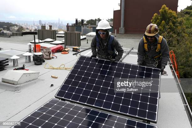 Luminalt solar installers Pam Quan and Walter Morales install solar panels on the roof of a home on May 9 2018 in San Francisco California The...