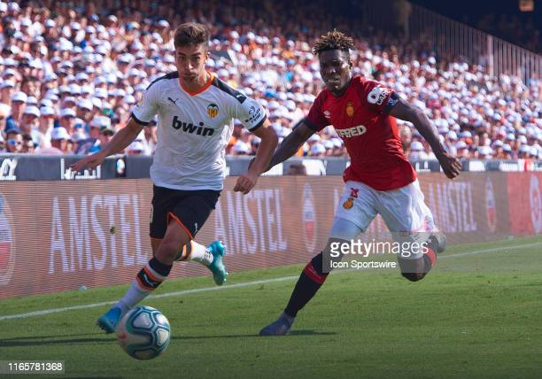 Lumor Agbenyenu defender of RCD Mallorca competes for the ball with Ferran Torres midfielder of Valencia CF during the La Liga match between Valencia...