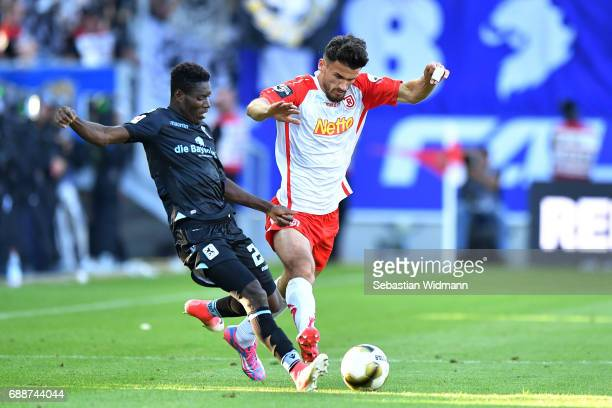 Lumor Agbenyenu of 1860 Muenchen and Haris Hyseni of Jahn Regensburg compete for the ball during the Second Bundesliga Playoff first leg match...
