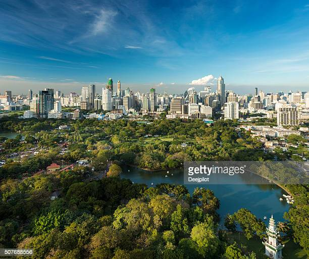 lumphini park and the downtown bangkok city skyline thailand - bangkok stock photos and pictures