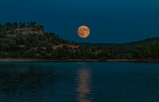 Luna llena sobre la laguna y entre las montañas - gettyimageskorea