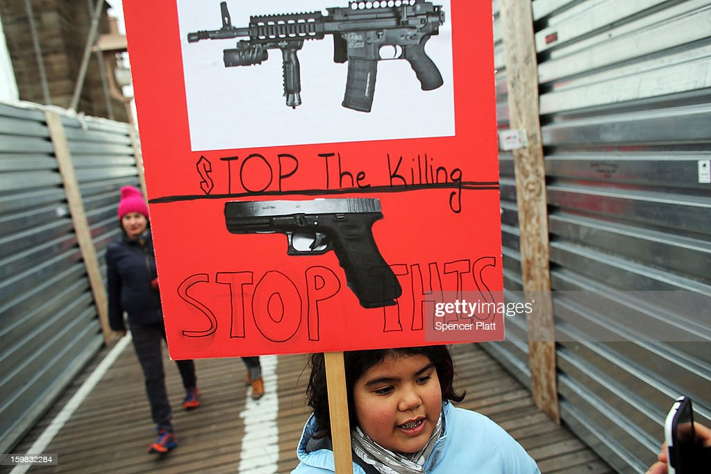 Luna Miller holds a anti gun sign while participating in a rally and march across the Brooklyn Bridge with One Million Moms for Gun Control, a gun control group formed in the wake of last month's massacre at a Newtown, Connecticut elementary school on January 21, 2013 in New York City. The group marched to City Hall where they held a rally and demanded stricter measures against guns. One Million Moms for Gun Control said the event is inspired by the Rev. Martin Luther King Jr.'s message of nonviolence.