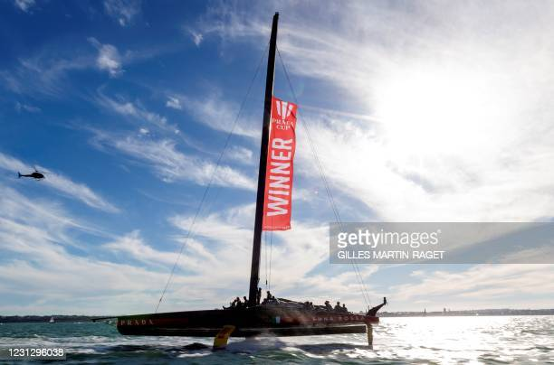 """Luna Rossa Prada Pirelli team fly a banner reading """"winner"""" as they celebrate victory in the Prada Cup final against INEOS Team UK in Auckland on..."""