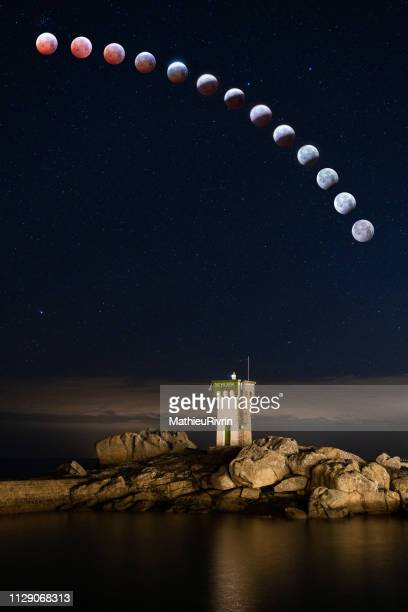 lunar eclipse behind trevignon lighthouse in bretagne - tour structure bâtie stock pictures, royalty-free photos & images