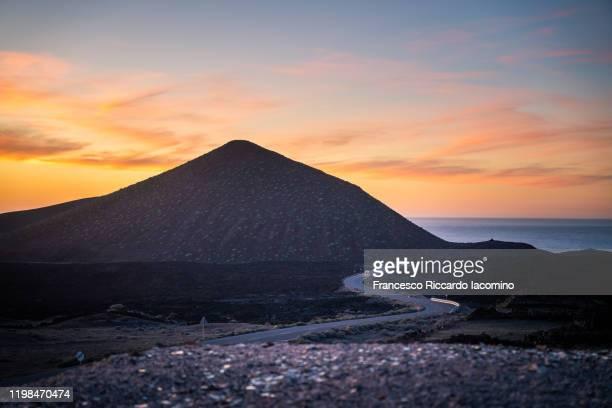 lunar landscape at sunset in lanzarote, canary islands. road to the sea - francesco riccardo iacomino spain foto e immagini stock