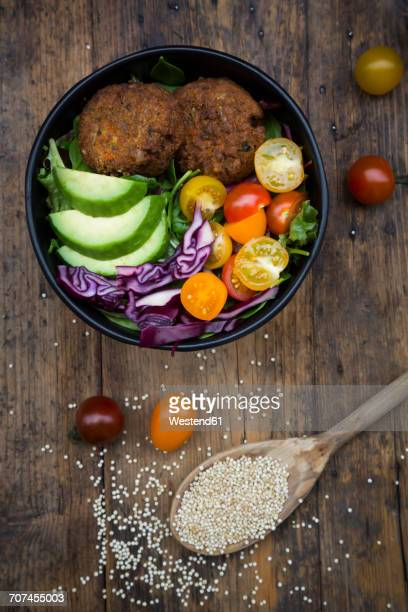 Lunch bowl of leaf salad, red cabbage, avocado, tomatoes and quinoa fritters