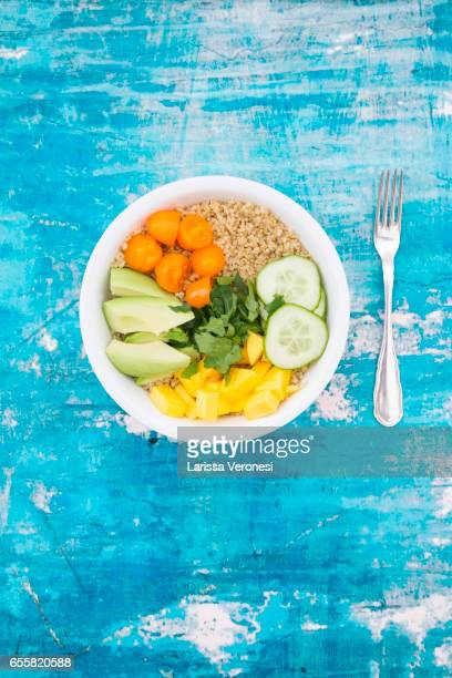 Lunch bowl of quinoa, mango, avocado, cucumber, orange tomatoes and parsley on blue surface
