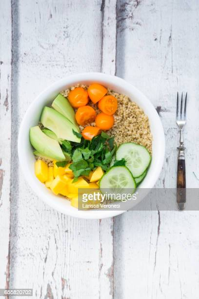 Lunch bowl of quinoa, mango, avocado, cucumber, orange tomatoes and parsley on wood