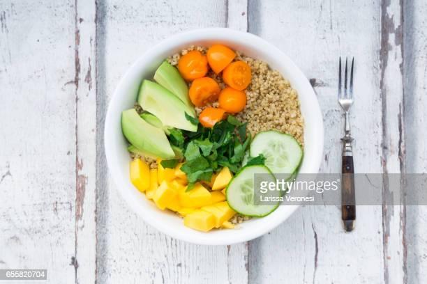 Lunch bowl of quinoa, mango, avocado, cucumber, orange tomatoes and parsley on wood