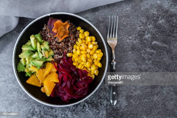Lunch bowl of red quinoa, beetroot, corn, avocado, orange and vegetable chips
