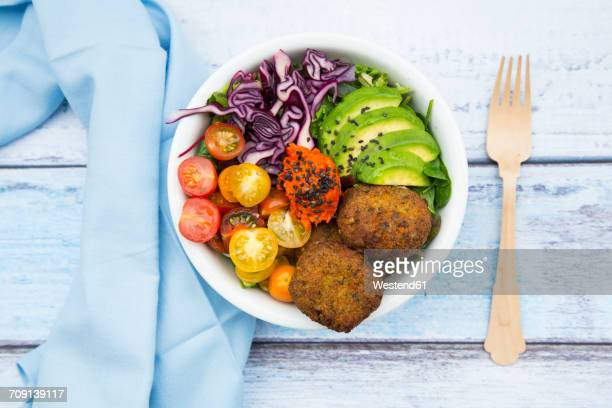 Lunch bowls of leaf salad, red cabbage, avocado, tomatoes, quinoa fritters and ajvar