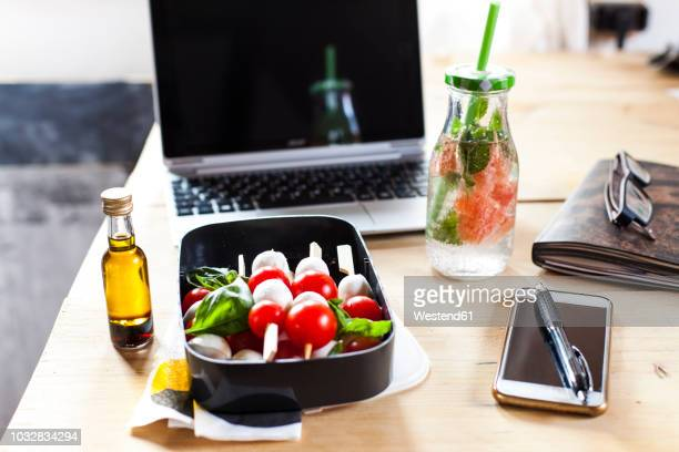 lunch box of caprese salad, bottle of infused water and laptop on desk - 昼食 ストックフォトと画像