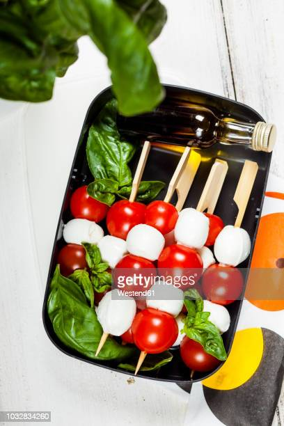 Lunch box of skewered cherry tomatoes and mozzarella cheese balls with basil leaves and vinaigrette