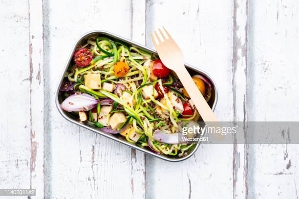 lunch box of zoodles with fried tofu, red quinoa, red onions and tomatoes - lunch box stock pictures, royalty-free photos & images