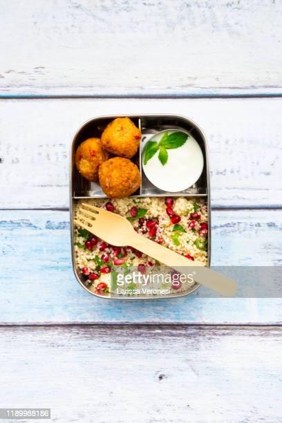 lunch box with falafel, couscous salad, and yoghurt sauce - larissa veronesi stock-fotos und bilder