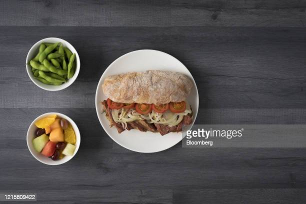 Lunch consisting of beef, onion and tomatoes on a ciabatta bread sandwich, a pot of edamame beans and fruit salad sits in this arranged photo in...