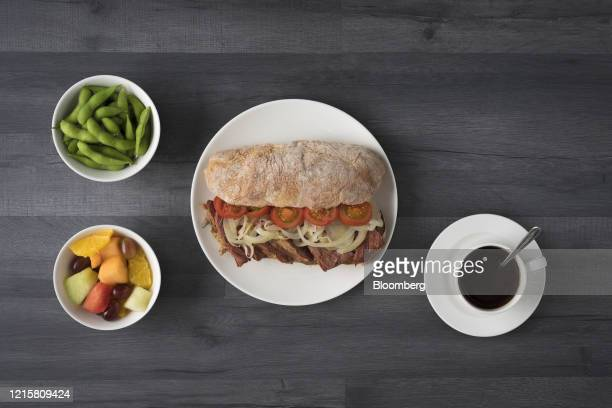 Lunch consisting of beef, onion and tomatoes on a ciabatta bread sandwich, a pot of edamame beans, fruit salad and a cup of coffee sits in this...