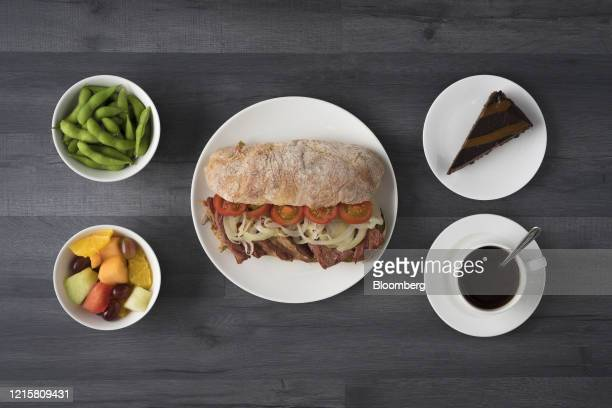 Lunch consisting of beef, onion and tomatoes on a ciabatta bread sandwich, a pot of edamame beans, fruit salad, a chocolate cheesecake and a cup of...