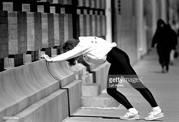 Lunch time runner uses th eside of the building of the downtown YMCA to do some stretching exercise before going on her run