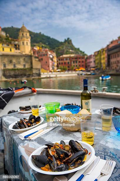 lunch with mussles and white wine on a boat in the port of vernazza. - リグーリア ストックフォトと画像