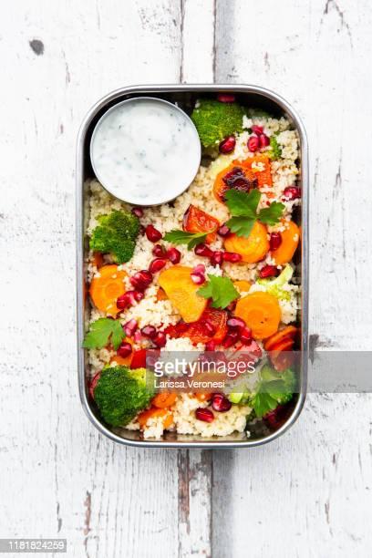 lunchbox with couscous, grilled vegetables, pomegranate seeds and yoghurt mint dip - larissa veronesi stock-fotos und bilder