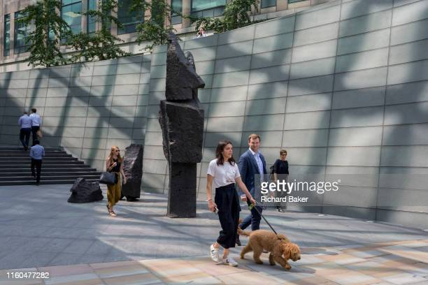 Lunchtime City workers walk through reflected light at Broadgate in the City of London the capital's financial district aka the Square Mile on 8th...